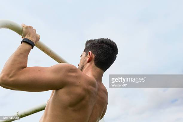 Athlete doing chin-ups outdoors