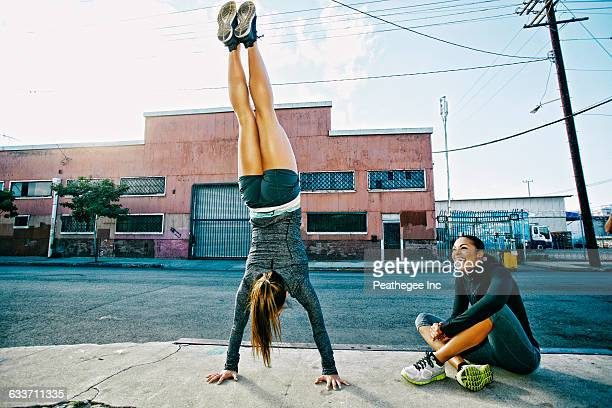 athlete doing handstand on sidewalk - handstand stock pictures, royalty-free photos & images