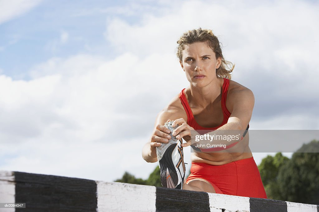 Athlete Doing Stretches on a Hurdle : Stock Photo