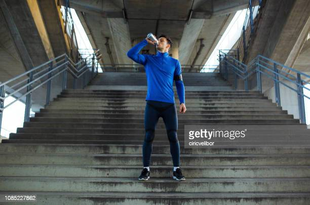 athlete drinking water and standing on the stairs - ritemprarsi foto e immagini stock