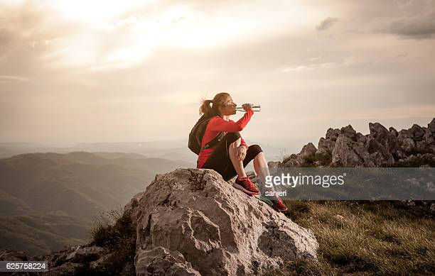 Athlete Drinking Water on the Top of the Hill