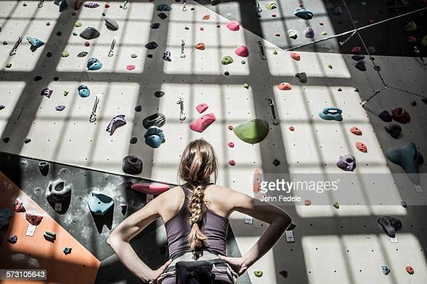 Athlete examining rock wall in gym