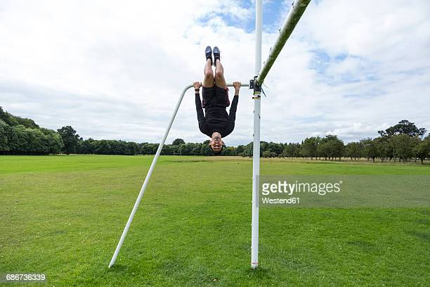 athlete exercising on goal on sports field - hanging stock pictures, royalty-free photos & images