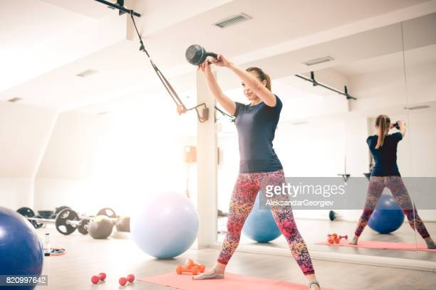 Athlete Female Doing Squats with Kettle Bell Weight in the Gym