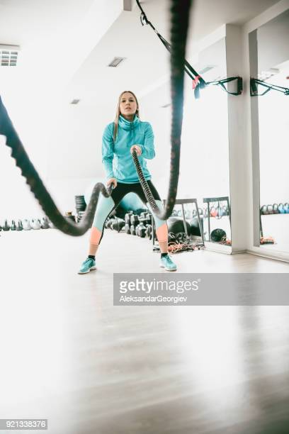 Athlete Female Make Battle Rope Exercise in the Gym