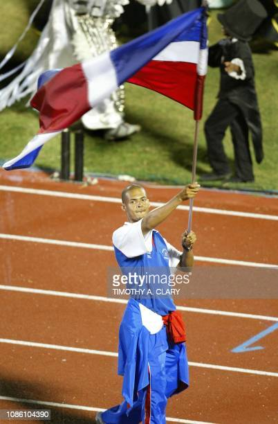 Athlete Félix Sanchez of Dominican Republic carries the flag during the opening ceremony of the XIV Pan American Games at the Olympic Stadium Juan...