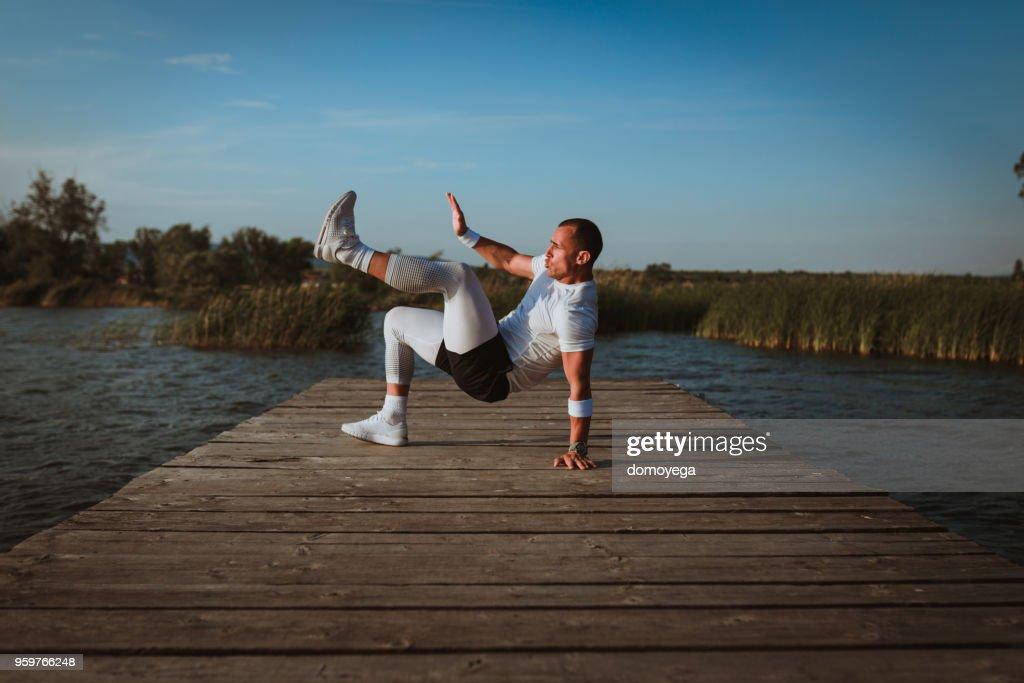 Sportler haben eine Übung in der Nähe von Wasser im freien : Stock-Foto
