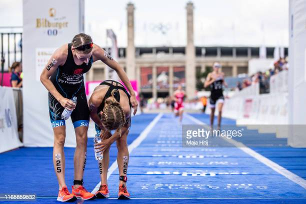 Athlete helps her team mate at the finish line during the National Championship in Triathlon Women on August 03 2019 near Olympiastadion in Berlin...