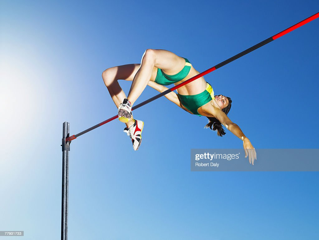 Athlete high jumping in an arena : Stock Photo
