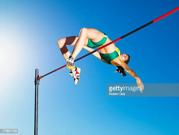 athlete high jumping in an arena - athletics stock photos and pictures