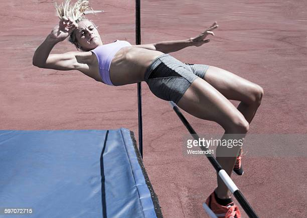 athlete high jumping - athletics stock photos and pictures