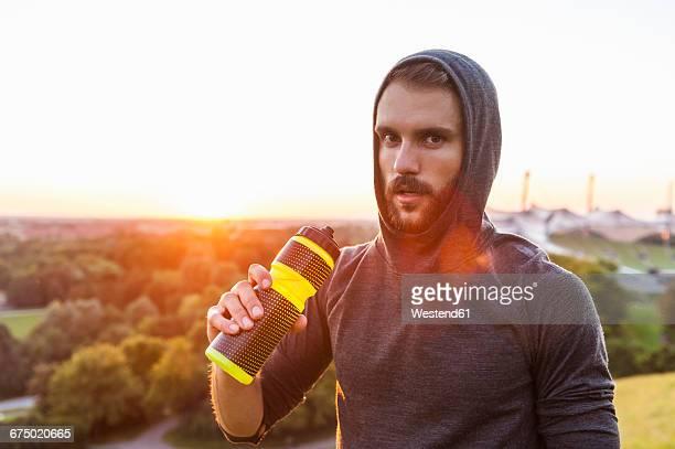 Athlete holding bottle at sunset
