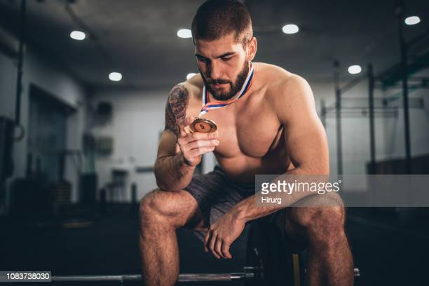 athlete holding his medal - medalist stock pictures, royalty-free photos & images
