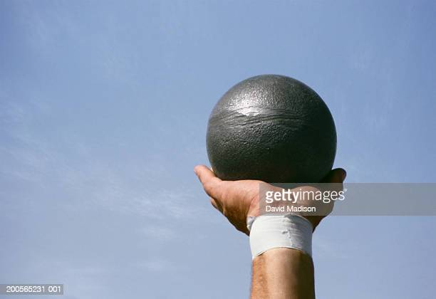 athlete holding shot put, only arm visible - shot put stock pictures, royalty-free photos & images