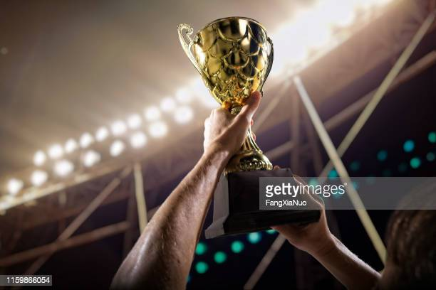 athlete holding trophy cup above head in stadium - trophy stock pictures, royalty-free photos & images