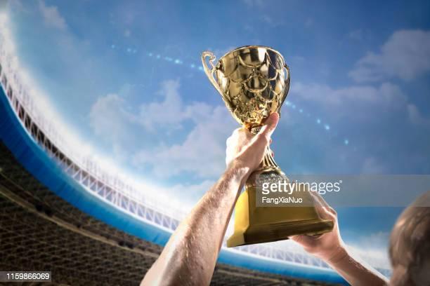 atleet holding trophy cup boven het hoofd in het stadion - the championship voetbalcompetitie stockfoto's en -beelden