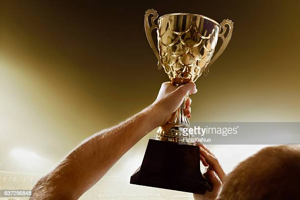 Athlete holding trophy cup above head in stadium