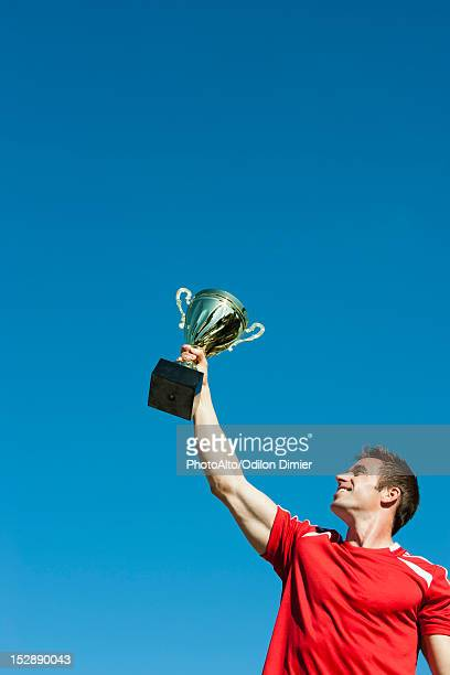 Athlete holding up trophy