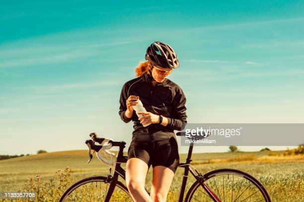 Athlete holds water bottle during break from riding her racing bicycle