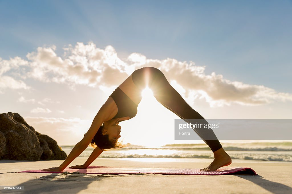 Athlete in downward facing dog position on shore : Photo