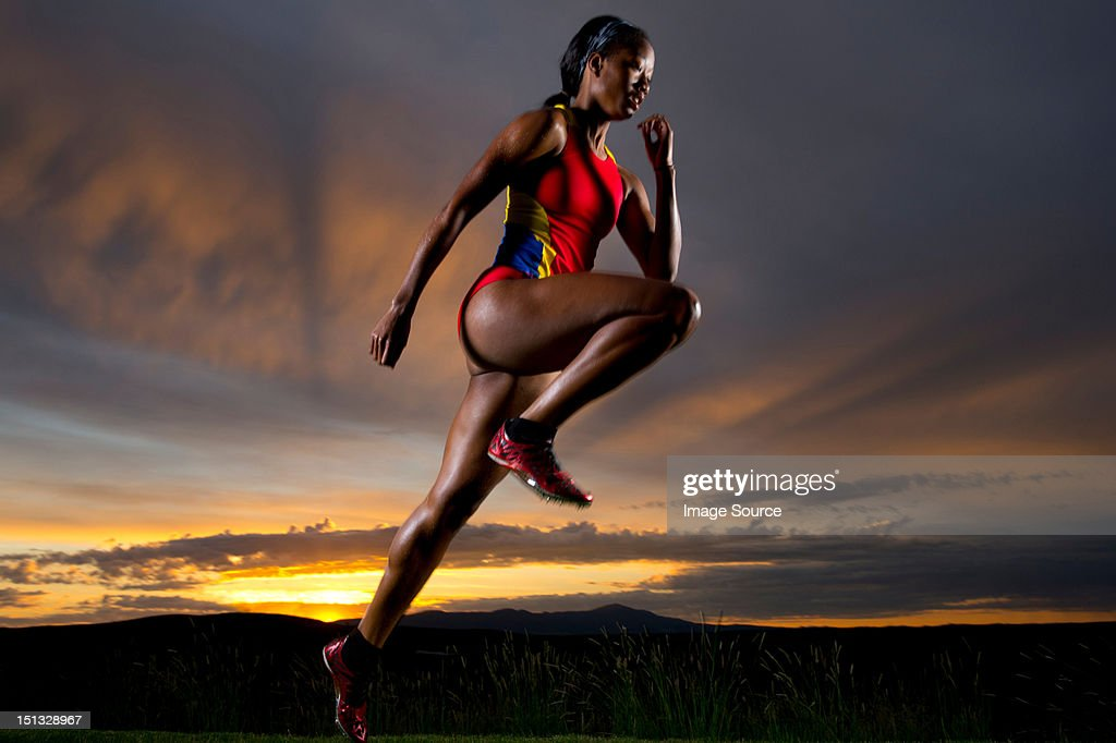 Athlete in mid air against sunset : Stock Photo