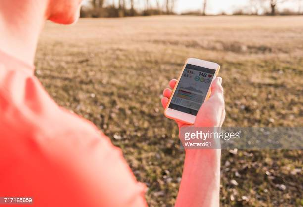 Athlete in rural landscape checking data on cell phone