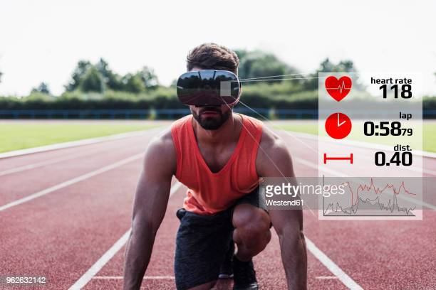 athlete in starting position on tartan track with data emerging from vr glasses - digital composite stock-fotos und bilder