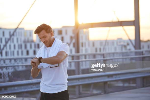 athlete in the city looking on smartwatch - sport stock-fotos und bilder