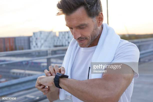 Athlete in the city looking on smartwatch