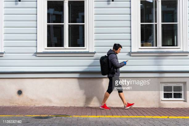 athlete in the city on the go with cell phone and headphones - roupa desportiva imagens e fotografias de stock