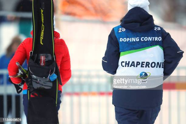A athlete is escorted by a official doping control chaperone after the IBU Biathlon World Championships Women 75km Sprint at Swedish National...