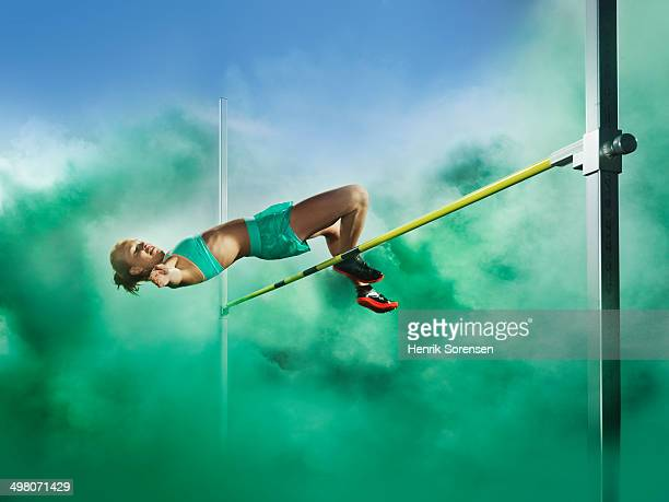 athlete jumping high jump in smoke