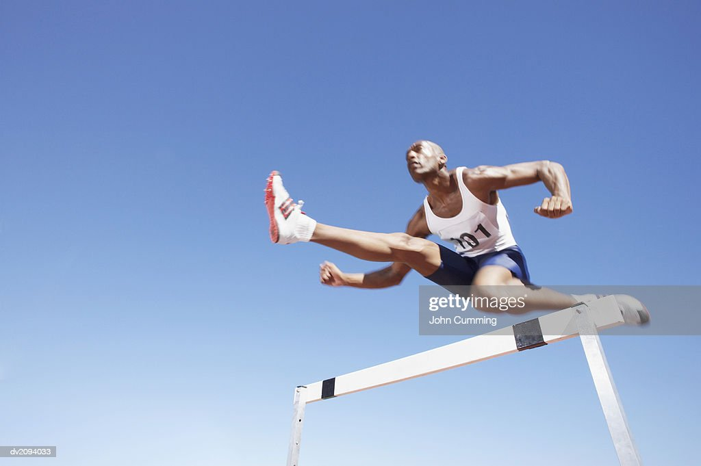 Athlete Jumping Over a Hurdle : Stock Photo