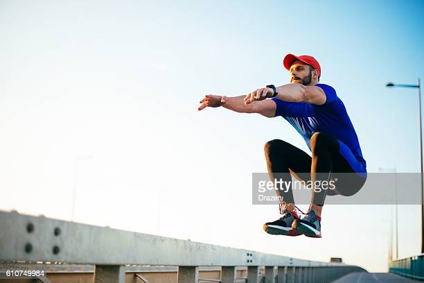 Athlete jumping over barriers during parkour training