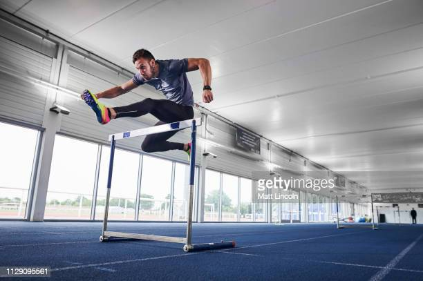 athlete jumping over hurdle on indoor running track - performance stock pictures, royalty-free photos & images