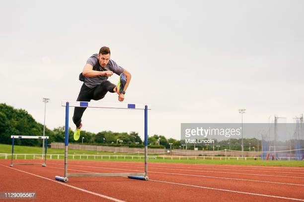 athlete jumping over hurdle on running track - athlete stock pictures, royalty-free photos & images