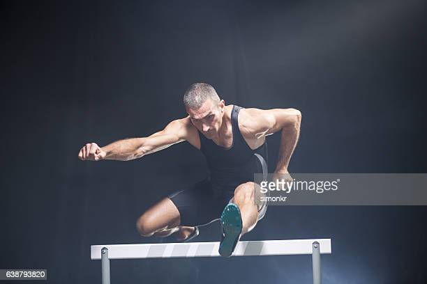 Athlete jumping over hurdle