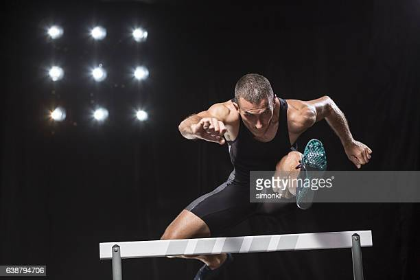 athlete jumping over hurdle - hurdling stock photos and pictures