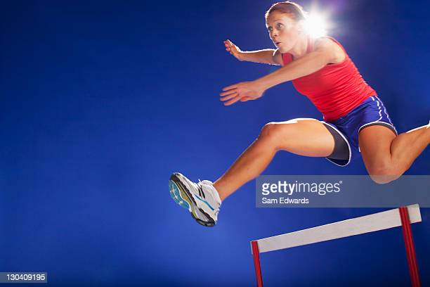Athlete jumping over hurdles