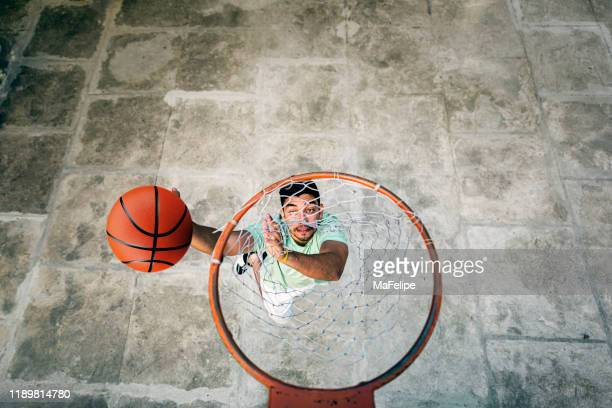 athlete jumping to score in basketball - basketball hoop stock pictures, royalty-free photos & images