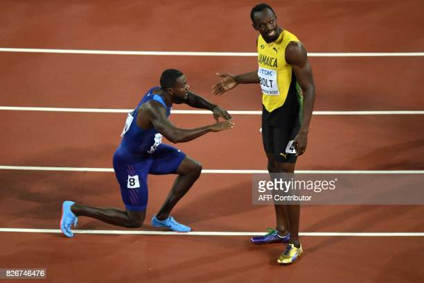 US athlete Justin Gatlin kneels in front of Jamaica's Usain Bolt after Gatlin won the final of the men's 100m athletics event at the 2017 IAAF World...