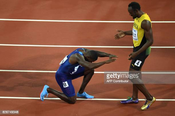 TOPSHOT US athlete Justin Gatlin kneels in front of Jamaica's Usain Bolt after Gatlin won the final of the men's 100m athletics event at the 2017...