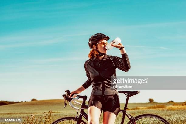 Athlete keeps hydrated by drinking water during break from cycling