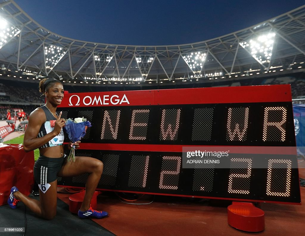 US athlete Kendra Harrison poses for a photograph with the clock showing her new world record time of 12.20 after she wins the final of the women's 100m hurdles at the IAAF Diamond League Anniversary Games athletics meeting at the Queen Elizabeth Olympic Park stadium in Stratford, east London on July 22, 2016. / AFP / Adrian DENNIS
