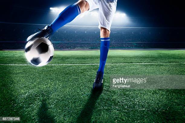 athlete kicking soccer ball in stadium - passing sport stock pictures, royalty-free photos & images