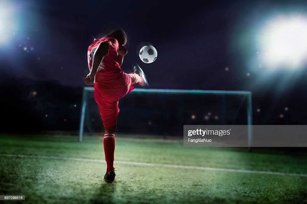 Athlete kicking soccer ball into a goal : Bildbanksbilder