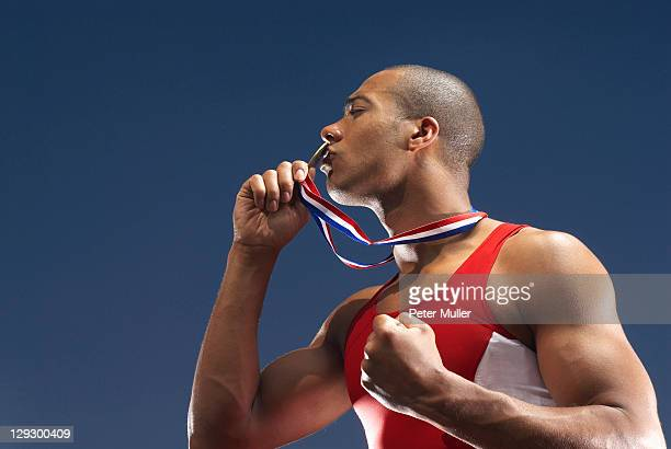 Athlete kissing medal outdoors