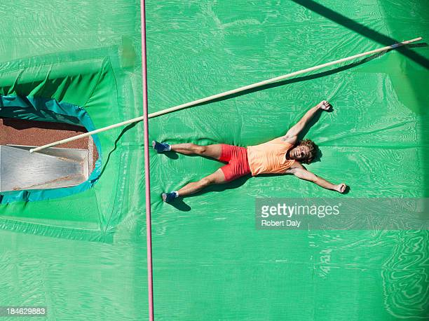 Athlete laying and cheering on crash mat after a pole vault