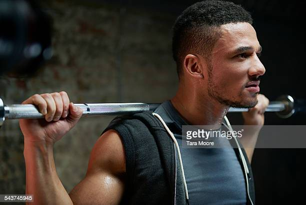 Athlete lifting weight bar against brick wall