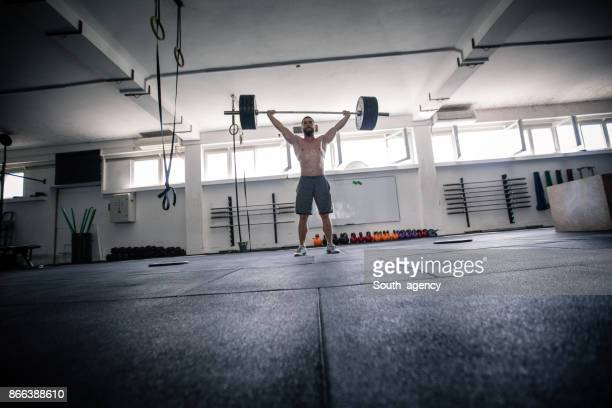 athlete lifting weights in the gym - snatch weightlifting stock photos and pictures